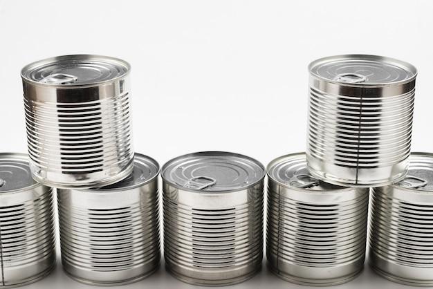 Groep zilver ingeblikt voedsel op witte achtergrond.