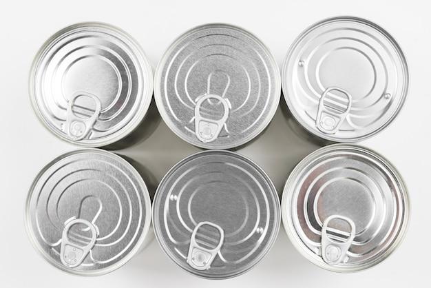 Groep zilveren ingeblikt voedsel op witte achtergrond.