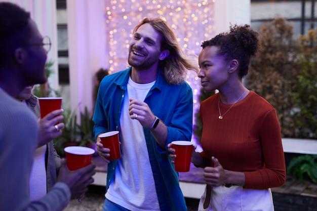 Groep zorgeloze jonge mensen genieten van een nachtfeest buiten op het dak verlicht door gekleurde lichten