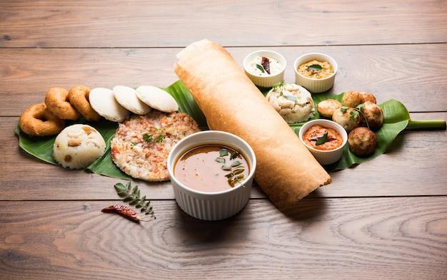 Groep zuid-indiaas eten zoals masala dosa, uttapam, idli of werkeloos, wada of vada, sambar, appam, griesmeel halwa, upma geserveerd over bananenblad met kleurrijke chutneys, selectieve focus