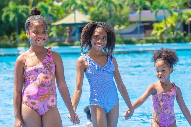 Groep zwarte kinderen die in het hete zomerseizoen gelukkig waterzwembadpark spelen