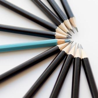 Groep zwarte potloden en één blauw potlood