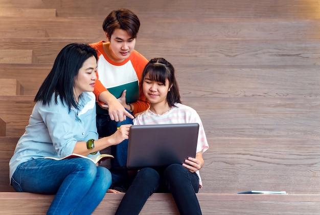 Groepen aziatische tienerstudenten die laptop computer met behulp van die samen bestuderen
