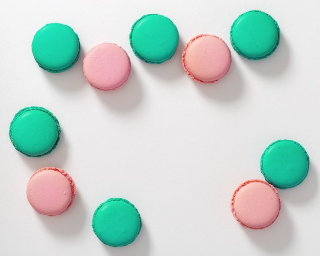 Groepen smakelijke makaronkoekjes van groen en roze op wit