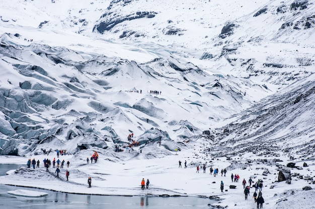 Groepen wandelende toeristen die in de sneeuwwitte ruige bergen wandelen