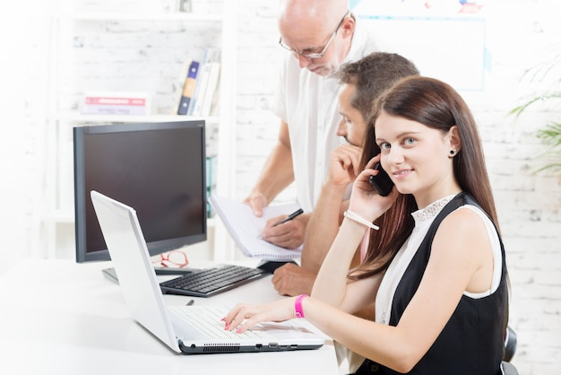 Groeps bedrijfsmensen in bureau, vrouw met laptop