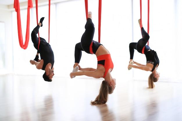 Groeps yoga-prestaties met rood linnen en beenuitrekken