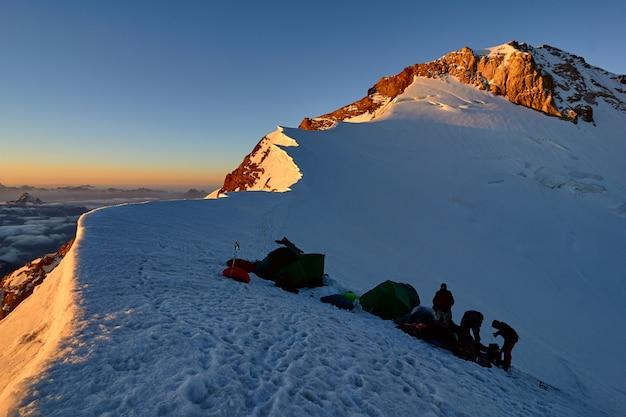 Groepsalpinisten in basiskamp op sneeuw piekplaatsentent bij zonsondergang, tadzjikistan