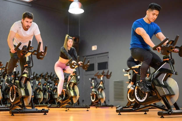 Groepsfietsen op een moderne fitnessfiets tijdens groepsles spinning in de sportschool