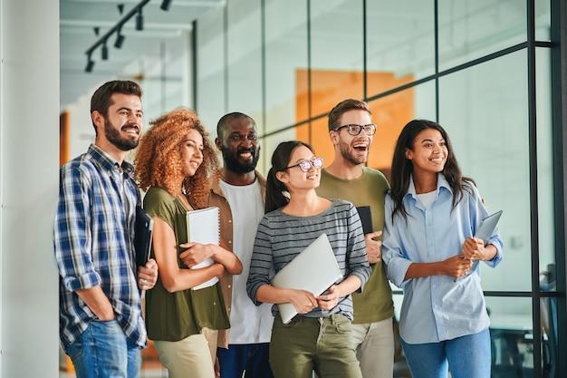 Groepsfoto van enthousiaste jongeren met laptops
