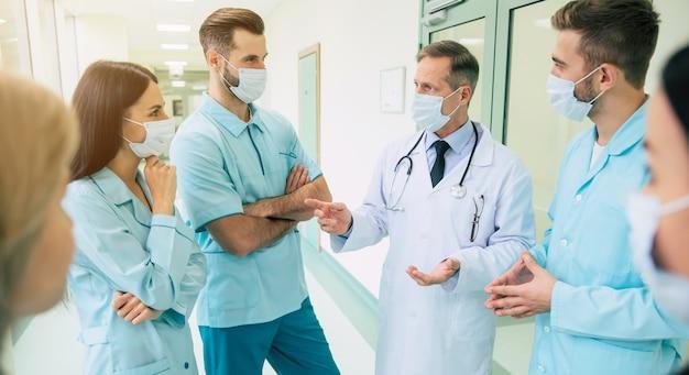 Groepsfoto van jonge medici tijdens een gesprek met de senior zelfverzekerde arts in de ziekenhuisgang