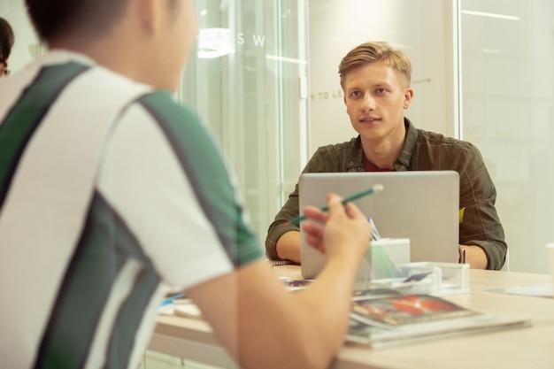 Groepslessen. geconcentreerde blonde man zit tegenover zijn computer en communiceert met zijn klasgenoot