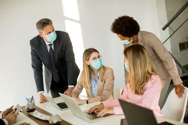 Groepsmensen uit het bedrijfsleven hebben een vergadering en werken op kantoor en dragen maskers als bescherming tegen coronavirus