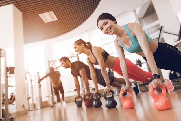 Groepsoefening mensen duwen op de halters in de sportschool.