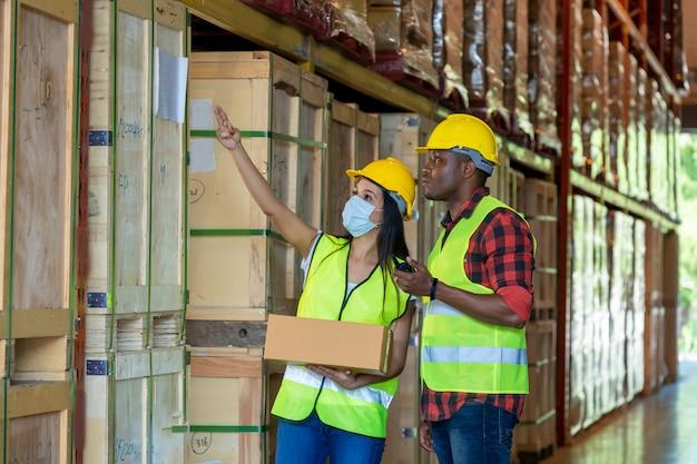 Groepspakhuisarbeiders die beschermend masker dragen die in industriële fabriek of pakhuis werken.