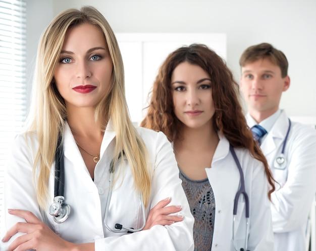 Groepsportret van artsen team staan met hun armen gekruist op de borst klaar om te werken. gezondheidszorg, medisch en teamwerkconcept.