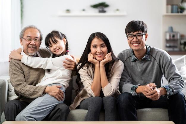 Groepsportret van aziatische en gelukkige familie zittend op de banklaag in de woonkamer met een glimlach