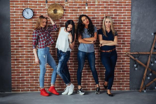Groepsportret van beste vriendenmeisjes met kleurrijke modieuze kleding die vriend het stellen op een bakstenen muur houden, stedelijke stijlmensen die pret hebben, s over de levensstijl van de jeugdsamenhorigheid