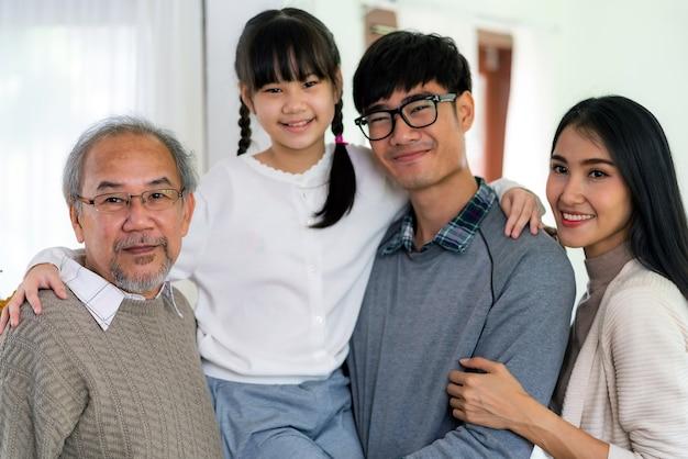Groepsportret van gelukkige multigenerationele aziatische familie staande in de woonkamer