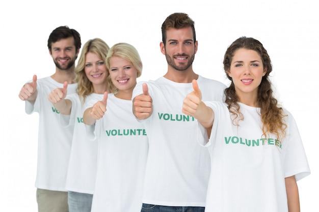 Groepsportret van gelukkige vrijwilligers die duimen omhoog gesturing