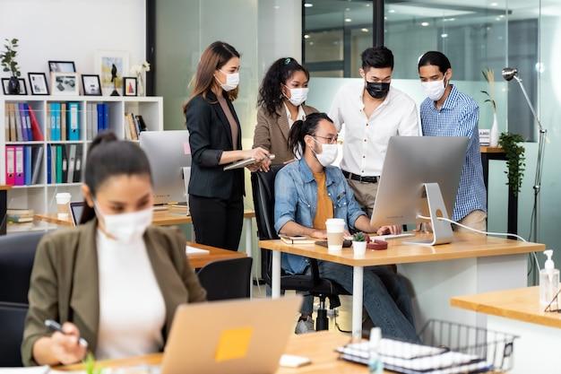 Groepsportret van interraciaal bedrijfsmedewerker draagt een beschermend gezichtsmasker in een nieuw normaal kantoor met praktijk op sociale afstand om verspreiding van coronavirus covid-19 te voorkomen