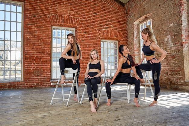 Groepsportret van jonge sportieve opgewonden mooie meisjes met oefeningsmatten die zich naast witte en muur bevinden die samen lachen spreken. spontane grappige studenten die wachten tot de klas begint. foto van volledige lengte