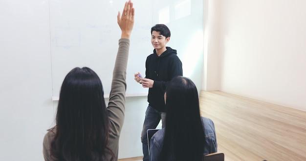 Groepsstudenten steken hun handen op om vragen aan een vriend te stellen voor lesgeven op het whiteboard in de klas