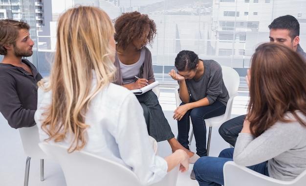 Groepstherapie sessie met een vrouw huilen