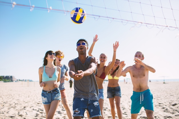 Groepsvrienden die bij beachvolleybal spelen