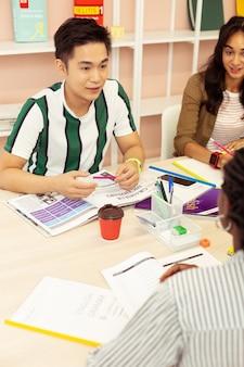 Groepswerk. geconcentreerde brunette man zit tegenover zijn leraar terwijl hij zijn taal oefent