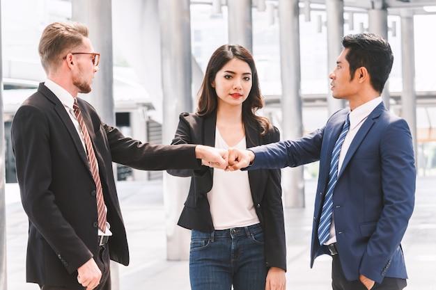 Groepswerk van zakenman en partner die de hand van de vuistbuil geven