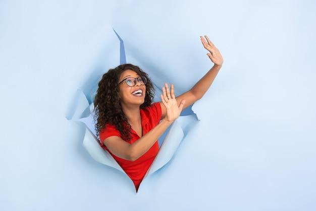 Groet die een vrolijke afro-amerikaanse vrouw op een gescheurde blauwe papieren achtergrond stopt