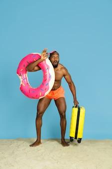 Groet. gelukkige jonge mens die met strandring als doughnut op blauwe studioachtergrond rust. concept van menselijke emoties, gezichtsuitdrukking, zomervakantie of weekend. chill, zomer, zee, oceaan.