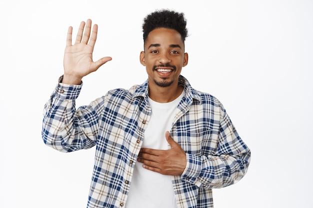 Groet. glimlachende vriendelijke afro-amerikaanse man vertelt zijn naam, steekt hand op en zet arm op borst, stelt zichzelf voor, zegt hallo, belooft, staande op wit.