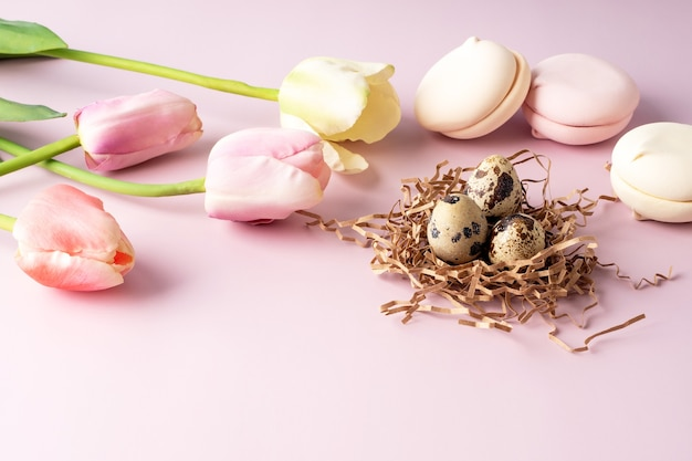 Groet pasen achtergrond. bloemen, tulpen, eieren, snoep op een roze achtergrond. gelukkig pasen.