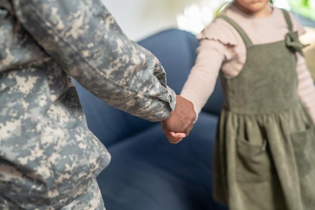 Groet. vader in militaire kleding handen schudden met zijn dochtertje tegenover de bank, geen gezichten zichtbaar