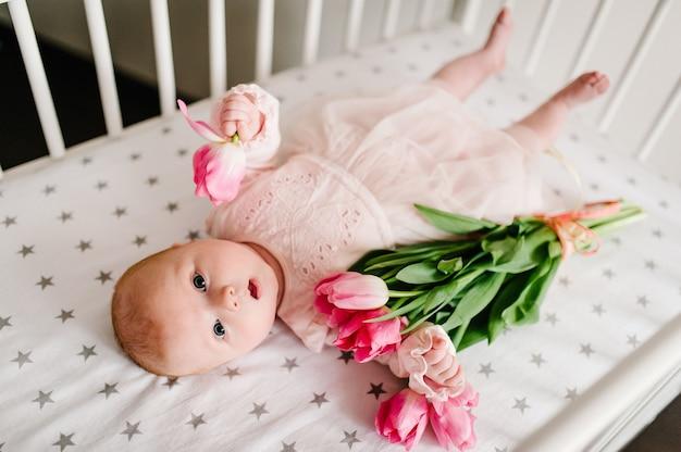 Groet voor de moeder met het pasgeboren babymeisje dat de bloem vasthoudt en op een bed ligt met een boeket roze tulpen. moederdag.