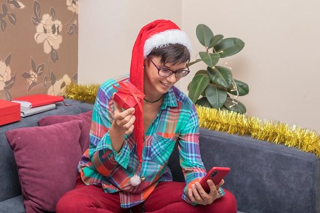 Groeten online kerst: vrouw thuis in een kerstmuts met cadeautjes spreekt online via smartphone