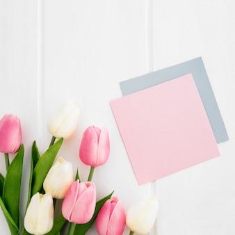 Groetkaart en tulpen op witte houten achtergrond voor de dag van de moeder