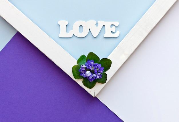 Groetkaart met blauwe bloemen en liefdecijfer op de kleurrijke document achtergrond.