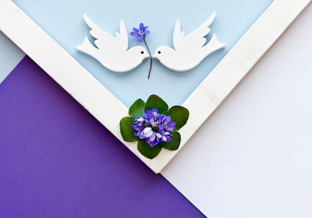 Groetkaart met blauwe bloemen en twee witte duiven op de kleurrijke document achtergrond.