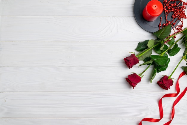 Groetkaart of achtergrondsamenstelling met rode rozen en kaars met copyspace. plat leggen
