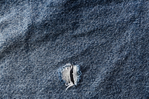 Grof denim oppervlak met scheur
