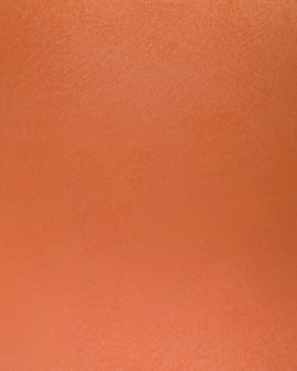 Grof oranje betonnen wandoppervlak