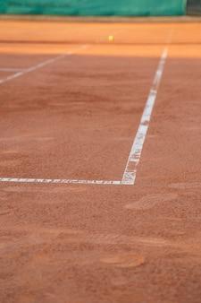 Grond op tennisbaan met witte lijnen bij daglicht.