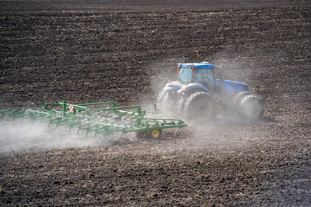 Grondbewerking in het veld met een tractor met een getrokken machine.