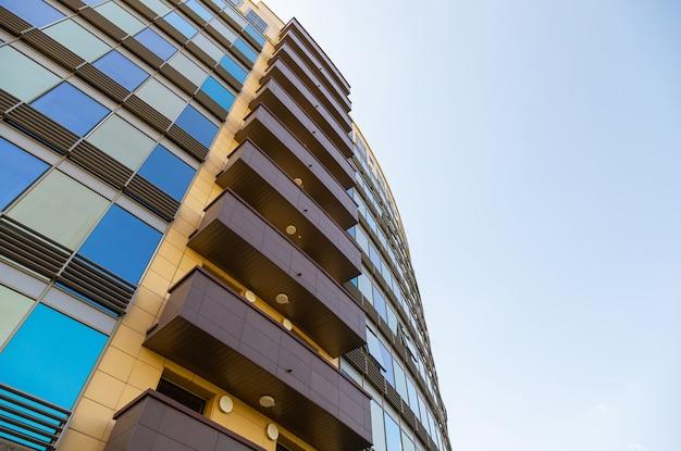 Grondmening van blauwe en gouden glasoppervlakte van de bouw van muur met vensters en bruine balkons