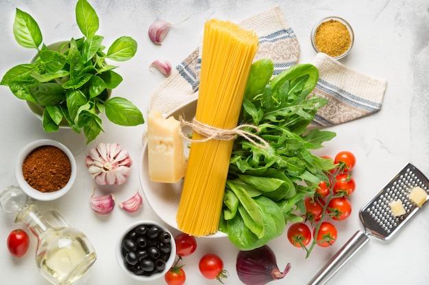 Grondstoffen voor het koken van spaghetti op een witte achtergrond. pasta, tomaten, knoflook, basilicum, parmezaan en olijven
