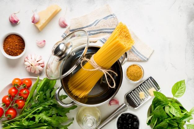 Grondstoffen voor het koken van spaghetti op een witte ondergrond