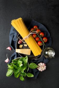 Grondstoffen voor het koken van spaghetti op een zwarte ondergrond
